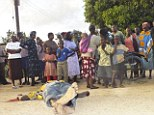 Brutal: Kenyan residents at the scene of one of the bodies of those killed in nearby Mpeketoni on Sunday. Police believe the Poromoko attack was carried out by the same group of Islamist militants