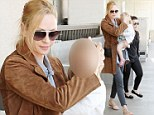 Uma Thurman clutches adorable daughter Luna in her arms as she walks through LA airport after teaming suede coat with denim shirt