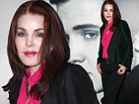 Her Good Luck Charm! Priscilla Presley poses in front of gigantic Elvis photo at convention in Las Vegas