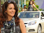 Soaring good time! Tina Fey stands up through the sun roof of a car driven by Amy Poehler on set of their new film The Nest
