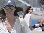 Minnie Driver covers up on the beach in Malibu in a white sun dress