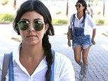 Pregnant Kourtney Kardashian shows off her toned legs in cut-off denim dungarees and gladiator sandals