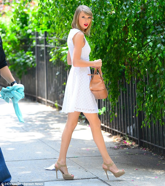 Simply angelic: Taylor cut a striking figure in a lace white dress paired with beige peep toe heels