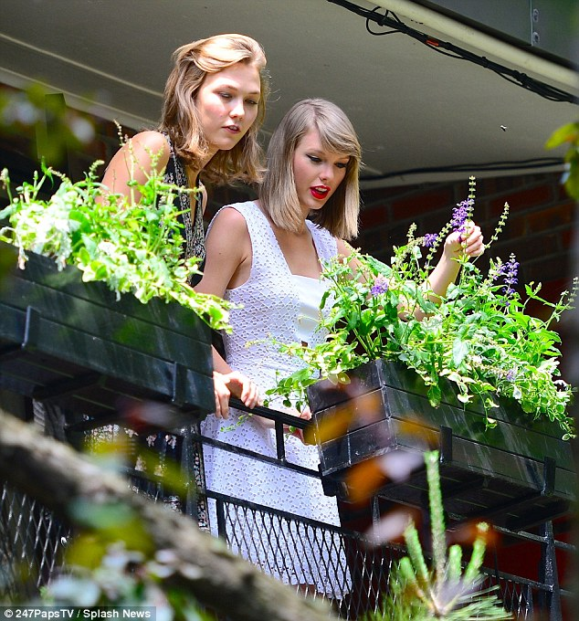 Going green: Taylor Swift and Karlie Kloss admired a potted plant upon a patio while in New York City on Friday