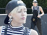 Quirky: Miley Cyrus let her signature style shine as she stepped out in leather dungarees over a black and white striped turtleneck crop top in Studio City, Los Angeles on Wednesday