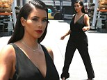 Va-va-voom! Kim Kardashian showcases her svelte figure in plunging black jumpsuit as she emerges from glamorous photo shoot in full hair and make-up