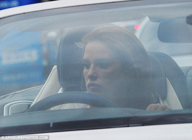 Taking its toll: The businesswoman looked glum as she sat behind the wheel of the white £100,000 motor