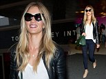 Rosie Huntington-Whiteley puts on another effortlessly stylish display in black biker jacket and snakeskin boots as she jets into LAX