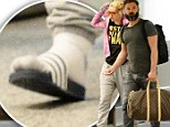 That's not Fancy footwear! Iggy Azalea hobbles through Miami airport in socks and 'slides' as she reveals she lost a toenail while playing soccer game