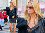 Street chic: Heidi Klum showed off her impressive figure in a black leather mini skirt and lacy blouse as she stepped out in New York's Soho neighbourhood on Friday