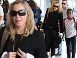 Madonna cuts an unusually demure figure in black jacket and cropped trousers as she jets into NYC with daughter Mercy