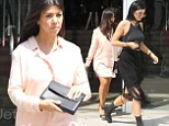 Pregnant Kourtney Kardashian covers up her growing baby bump in oversize shirt as she shops with Kylie in New York