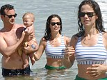 Pretty Little swimmers! Tammin Sursok shows off her bikini body splashing around in the ocean with husband Sean McEwen and adorable daughter Phoenix