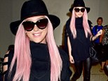 Kesha cuts an eclectic figure with bright pink hair, black hat and leather trousers as she arrives at LAX