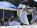 How relaxing! Minnie Driver reclines in the sand as she treats her son Henry to a day at the beach