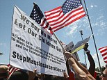 MURRIETA, CA - JULY 04:  A protester who opposes arrivals of buses carrying largely women and children undocumented migrants for processing at the Murrieta Border Patrol Station pushes his flag over the placard of a counter-demonstrator on July 4, 2014 in Murrieta, California. Earlier this week, protesters in the city turned away buses carrying about 140 immigrants that had been apprehended in Texas and flown to California for processing as Texas deals with an influx of immigrants. Federal officials estimate more than 50,000 minors, mostly from Central America, have been caught crossing the border since October 2013. (Photo by David McNew/Getty Images)