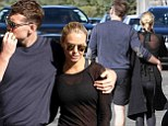 Why so modest, Lara? Bikini model Bingle comes over all coy as she hides her figure by wearing her coat BACKWARDS during stroll with beau Sam Worthington