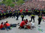 Costa Rican fans stand behind a police cordon after three people (lying) were injured while watching the Brazil 2014 FIFA World Cup football match against Netherlands on a giant screen at Democracy Square in San Jose on July 05, 2014.  AFP PHOTO/Ezequiel BECERRAEZEQUIEL BECERRA/AFP/Getty Images