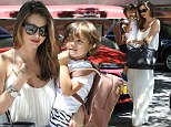 The white stuff: Miranda Kerr looks stunning in a sleeveless pastel dress as she arrives home with adorable toddle Flynn on Sunday in New York City
