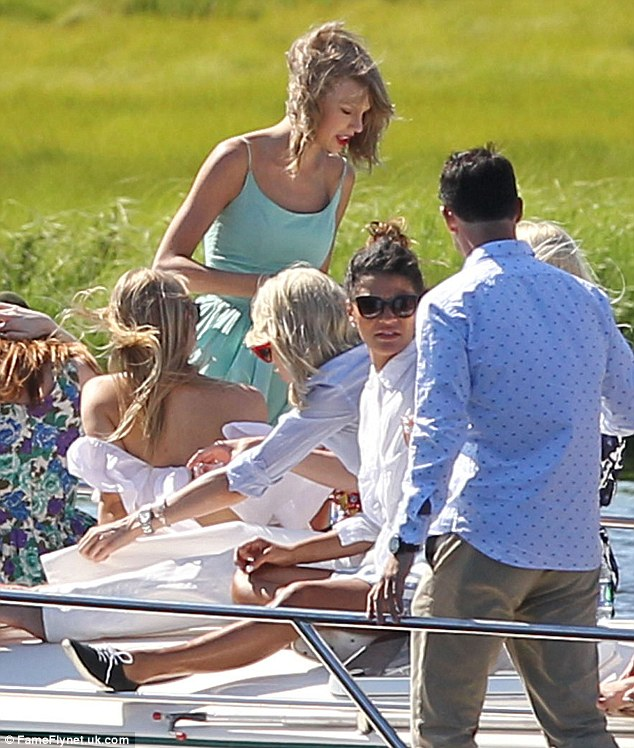 Too much fun: Emma Stone sat on the far left in floral whilst Taylor stood and had her pals pose