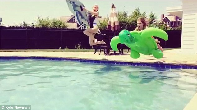 Here we go! In the video, the women are seen standing at the edge of a swimming pool each holding a flotation device before leaping into the water