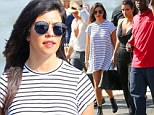 Pregnant Kourtney Kardashian displays her maternity style in striped T-shirt dress upon touch down in NYC with sister Kim