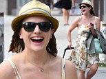 Life's no drag! Mad Men star Elisabeth Moss cackles with glee as she pulls along her own luggage in New York