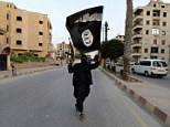 Militants in Iraq have seized nuclear materials used for scientific research at a university in Mosul. Pictured is a Isis member waving a flag in Raqqa, Syria, last month