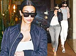 Kim Kardashian sports her favourite black bomber jacket and skin-tight grey jeans as she heads to the airport with model sister Kendall Jenner