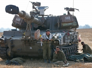 Israeli soldiers begin their day next to the mobile artillery unit on the Israel-Gaza border...