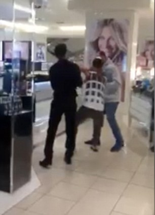 Resisting: The confused man sat on the floor as they dragged him along past the cosmetics counters