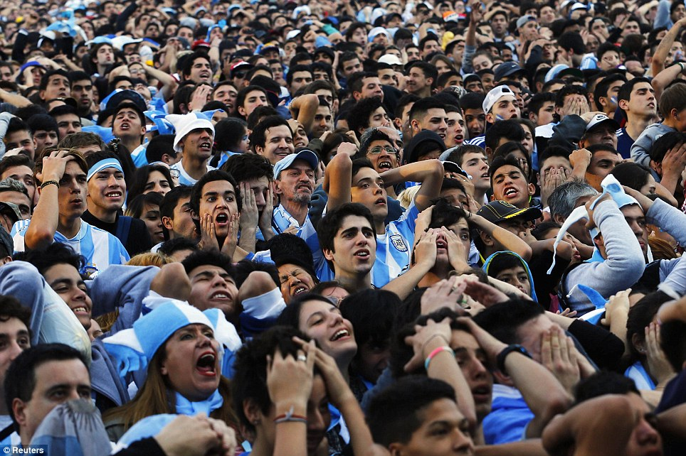 Despair: Argentina fans at a public screening of the final in Buenos Aires come to terms with the late defeat to Germany