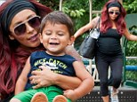 Pregnant Snooki displays her large baby bump in tight top as she swings with son Lorenzo at the park