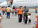 First wave: Women and their children walk on the San Pedro Sula airport tarmac after being deported from the U.S. as part of the first wave of immigrants being shipped back to Honduras, Guatemala and Salvador amidst the southern border immigration crisis