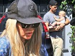 Fergie goes incognito in a black cap and sunglasses as doting dad Josh Duhamel cradles the couple's 10-month-old son Axl on LA outing