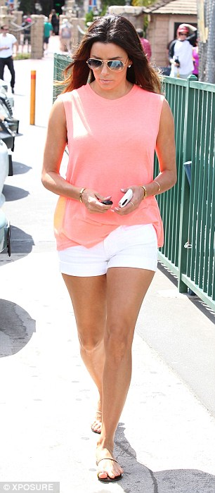 Summer casual: Showing off her muscular legs, the star donned a pair of short white shorts which she coordinated with a neon peach loose fitting top