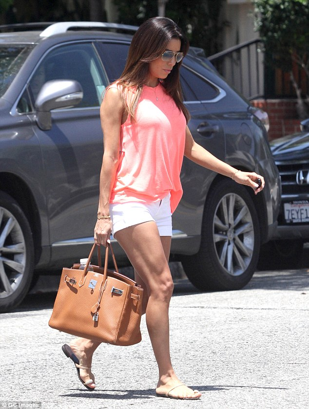 Expensive extras: Eva accessorised her look with a pair of aviator sunglasses, gold and diamond sandals and a brown Hermes handbag