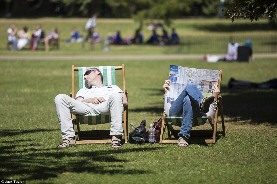 Checking the map: People sit in deckchairs as they relax at St James's Park in Central London