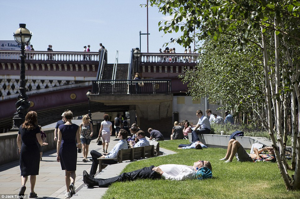 Sun in the sky: People sit next to the River Thames as Londoners head outside to enjoy the warm weather
