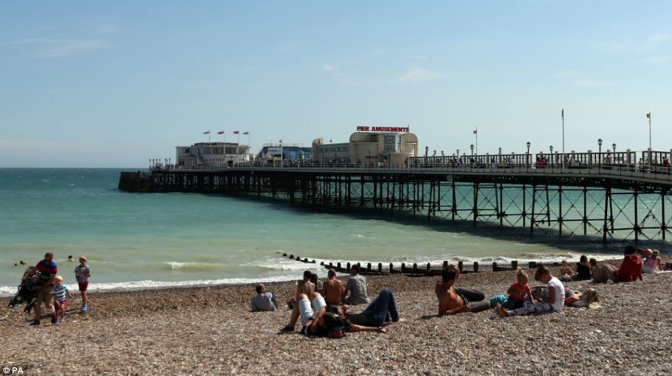 Seaside sun: People soaked up the sun yesterday on Worthing beach near the pier in West Sussex