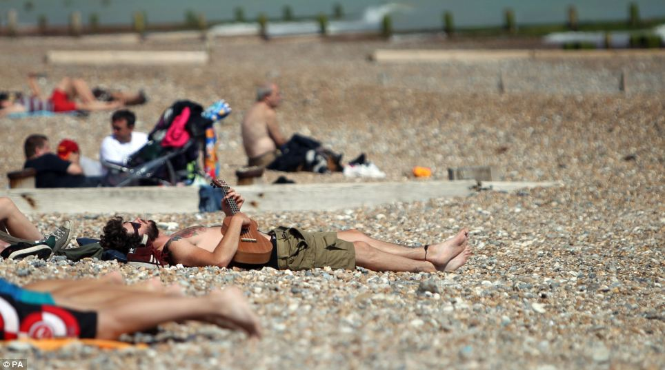 A musician on his guitar makes the most of the sun on Worthing beach, where the good weather is set to remain for a few days