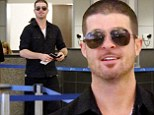 Smiling through the heartbreak! Robin Thicke cracks grin at airport despite dismal sales of new album Paula