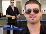 Smiling through the heartbreak! Robin Thicke cracks grin at airport despite dismal sales of new album Paula