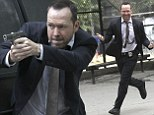 Action man! Donnie Wahlberg totes a prop gun as he shoots high-energy stunt scenes for his hit TV series Blue Bloods