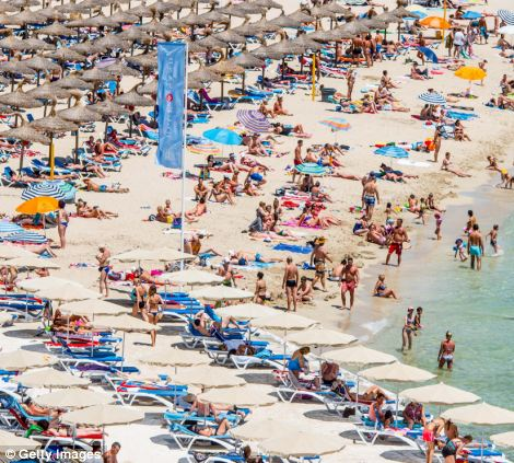 Tourists sunbathing at Magaluf beach