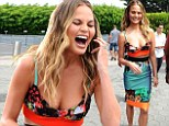 Chrissy Teigen leaves little to the imagination in racy low-cut ensemble as she larks around on Extra