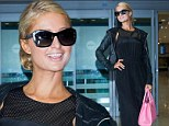 Covering up: Paris Hilton his her bikini body in a baggy black jumpsuit as she arrived at the Incheon International Airport in South Korea on Wednesday