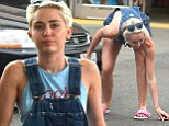 She's ready to pump it! Twerking sensation Miley Cyrus picks dollar bills off the floor... while filling up her Porsche at a gas station