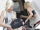 What marriage crisis? Tori Spelling makes a statement with a 'Mrs. McDermott' purse and flashes skin in a gaping shirt... as she steps out without Dean