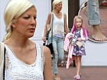 Forgot something? Busy mom Tori Spelling heads out of the house barefoot with pink-haired daughter Stella in tow